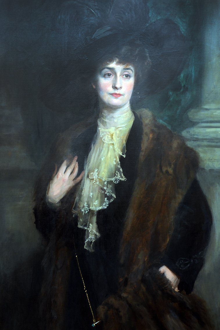 In a fur coat and black hat with feathers. Signed l.r. E Patry. Oil on canvas, 60 ins by 40 ins.