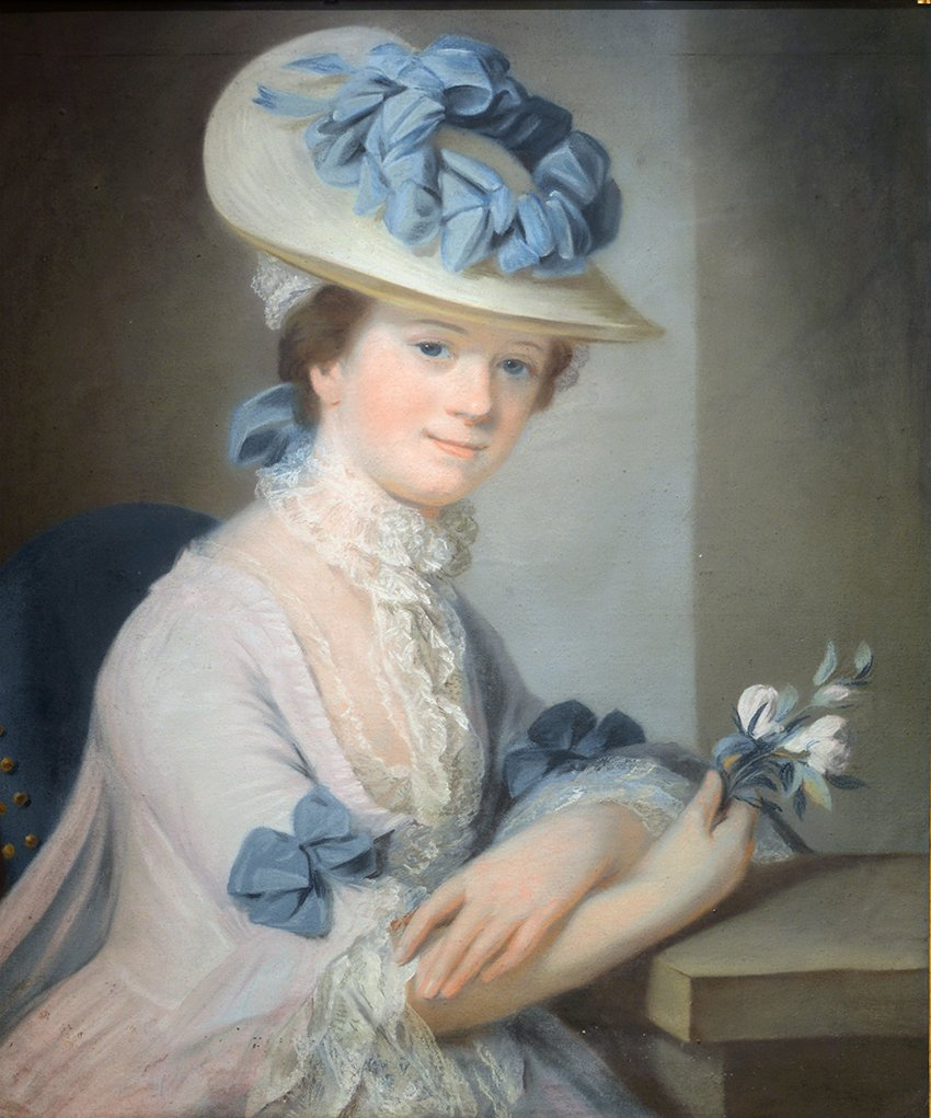 Half-length, wearing a pink satin dress with lace cuffs and blue ribbons, and a matching hat, holding flowers. Pastel behind glass. 28 3/4 ins by 23 ins.