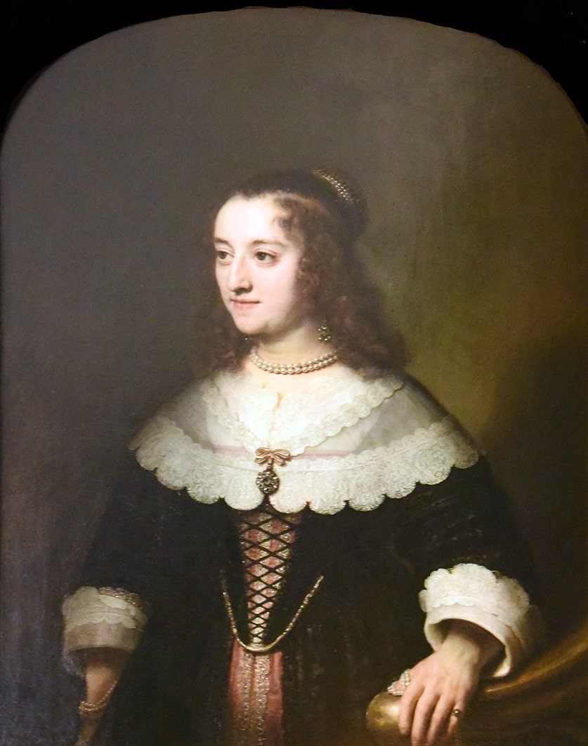 Wearing pearls, standing with her left hand on a balustrade(?)                                                 Inscribed Rembrandt ft/1644. Oil on panel, arched top. 37 1/4 ins by 29 1/2 ins.