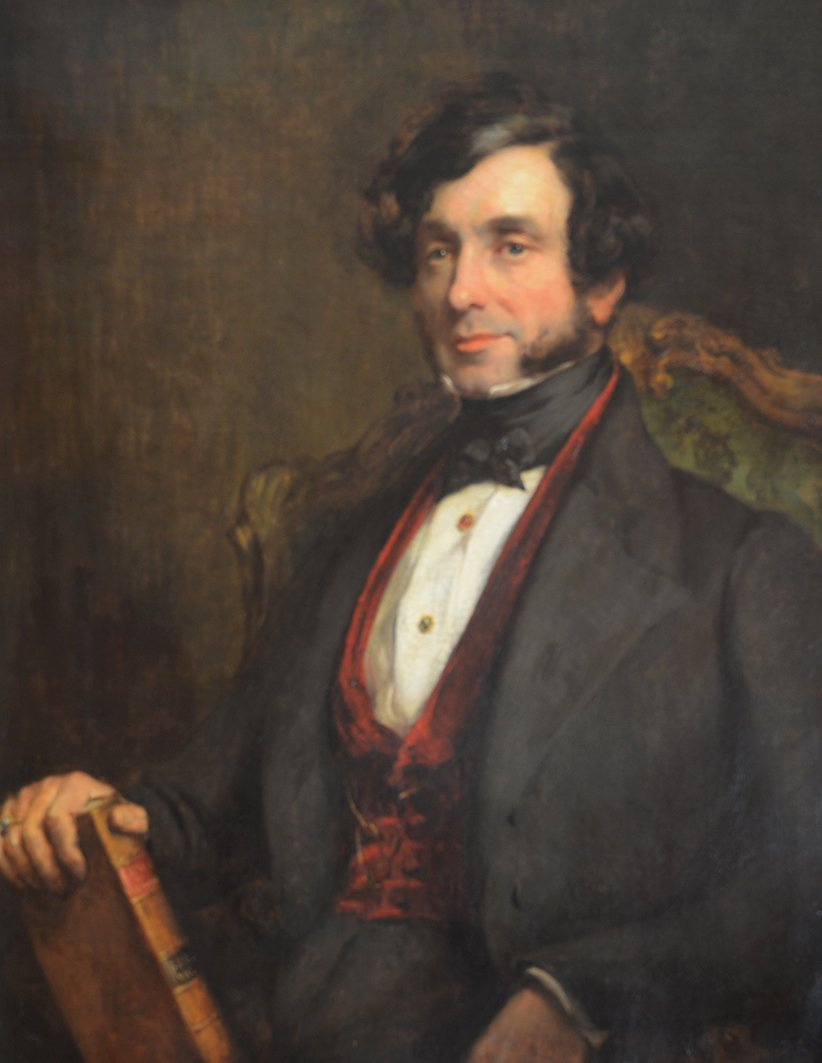 (7th Earl of Shaftesbury, 1801 - 1885): half length, wearing a grey coat and waistcoat, holding a volume of Acts of Parliament, possibly the Factory Act. Oil on canvas, in a contemporary frame, 34 3/4 ins by 26 1/2 ins.